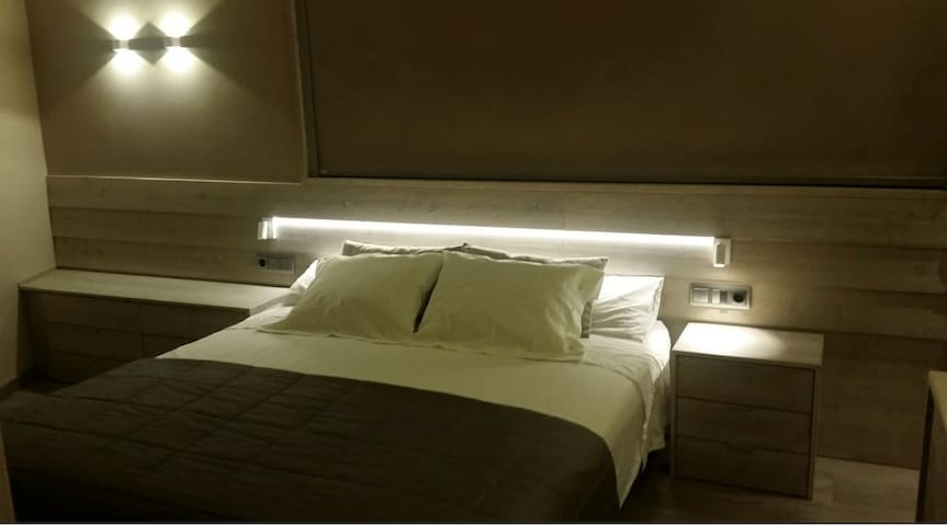 dormitorio principal con cama de matrimonio y lavabo, con salida a la terraza que tiene vistas a la montaña de Queralt.