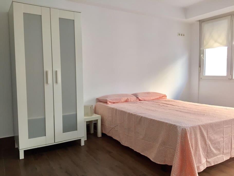 Amplio dormitorio con con cama de matrimonio y cama de 90, mesitas y armario.