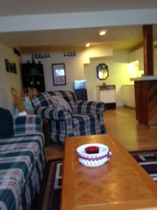 Living room has sofa, easy chair and loveseat including look at kitchen area