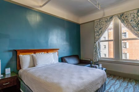 Room with Queen Bed with New Bedding.   End table with LED lamp with USB charging ports.