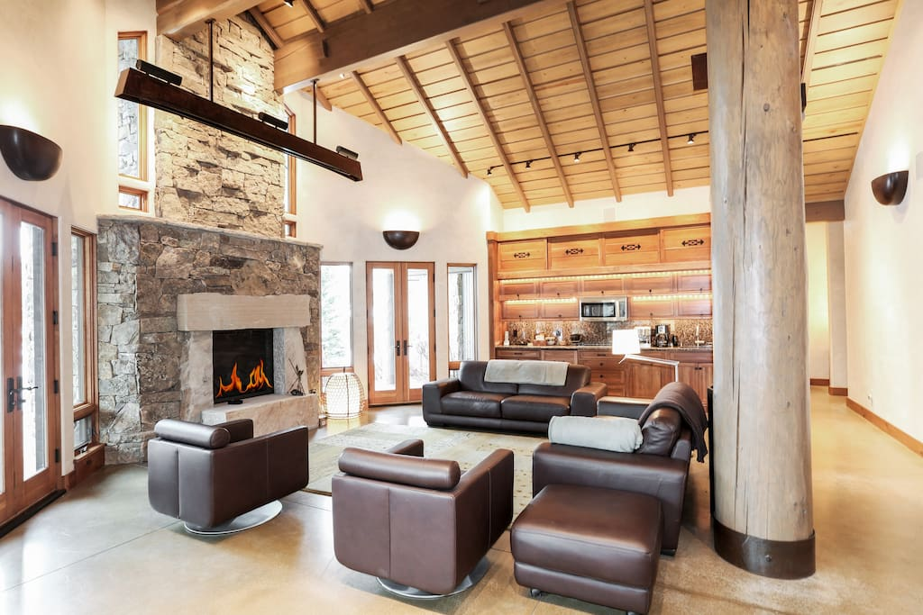 """Impressive living area features plenty of seating around a fireplace and 100"""" projection screen. Home is professionally cleaned by housekeeping staff."""