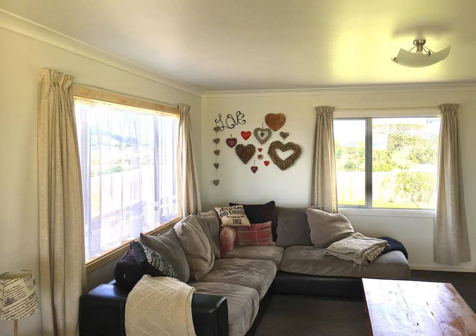 Very large light airy lounge with comfy sofa and lazy boys - bifold doors leading out onto a large deck with views over the Pacific Ocean, Whale and White Island