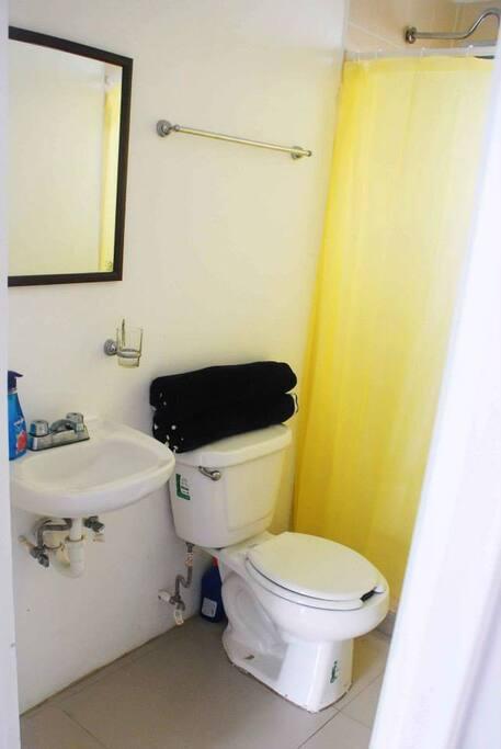 El baño cuenta con agua caliente, wc, espejo y lavabo