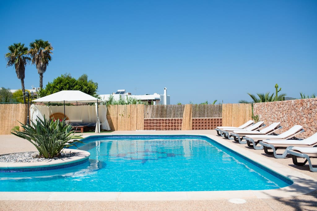 Pool with sunbeds and gazebo with comfortable seating and coffee table