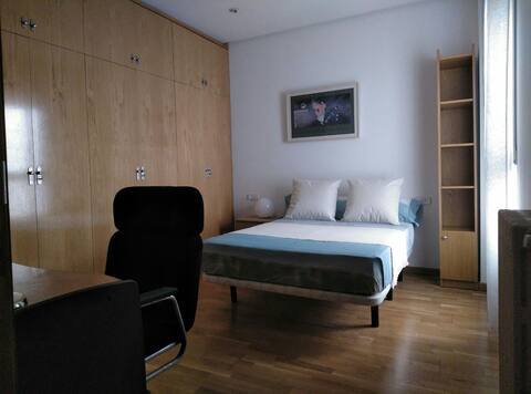 Double room with bedside table and night lamp, wardrobe, TV, desk, lamp and chair.