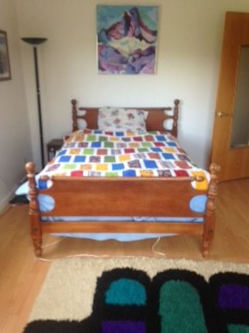 This room has laminate floors, two windows, homemade quilt on full bed.