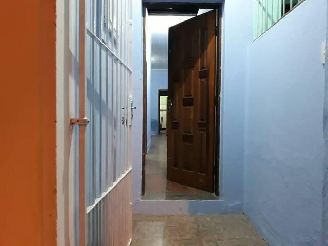Entrada da casa: portão de grade e porta com chave tetra.