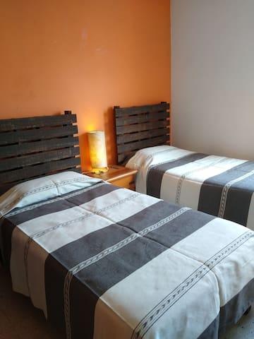 Habitación doble cama individual,  planta alta con ventana, closet, baño compartido, tv, buró central y lámpara de lectura, ventilador vertical y cortinas gruesas para obscurecer la habitación y así lograr un mejor descanso.