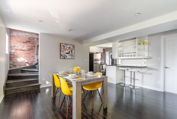 Dining area and kitchen plus exposed brick on staircase walls