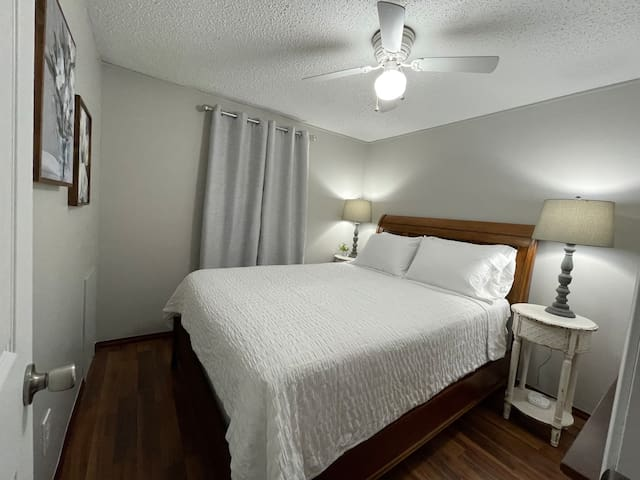 Bedroom 2 contains a queen bed. Each nightstand has a lamp and charging station for AC adapters and USB.