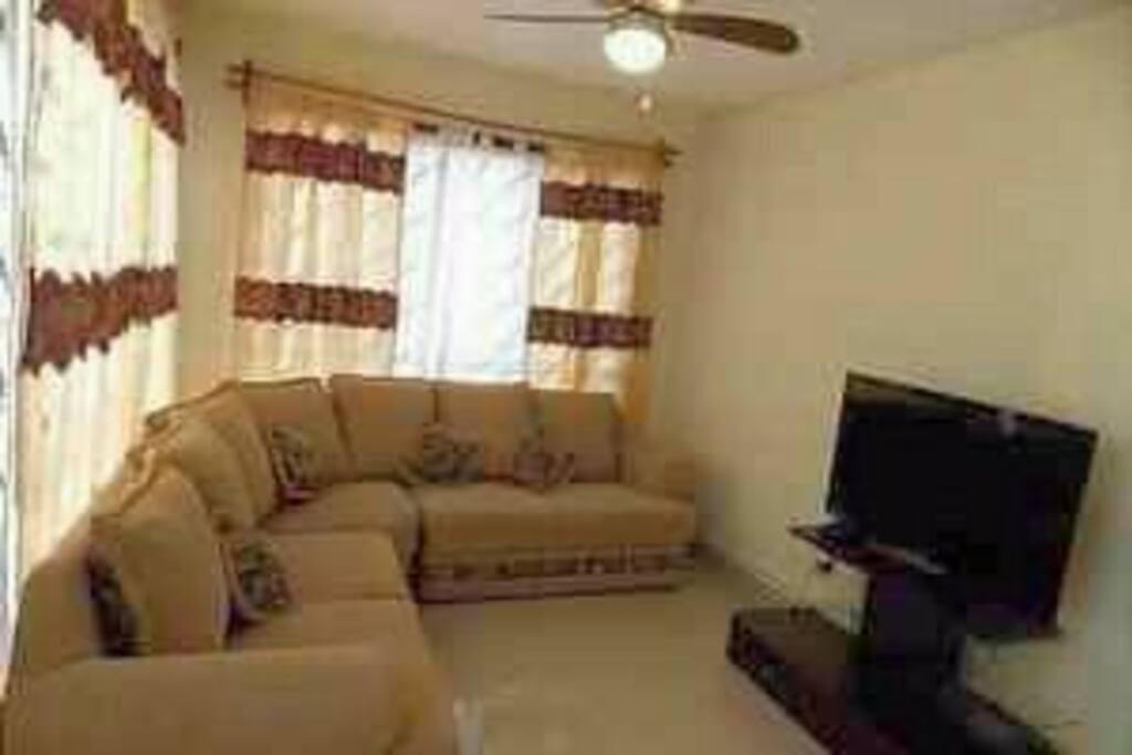 Sala cómoda y con bastante luz, ventiladores de techo y TV con cable