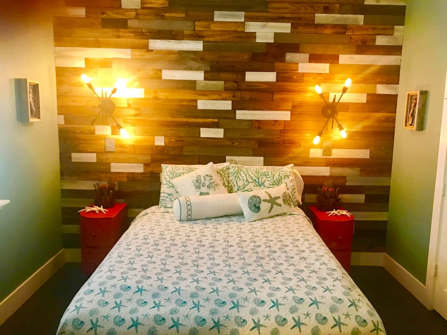 Queen size  comfy bed  in suite with wood paneled wall and funky light fixtures.