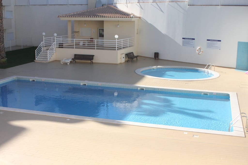 Swimming pool for adults and childrens, with support bar and grass for relax and sunbathing.