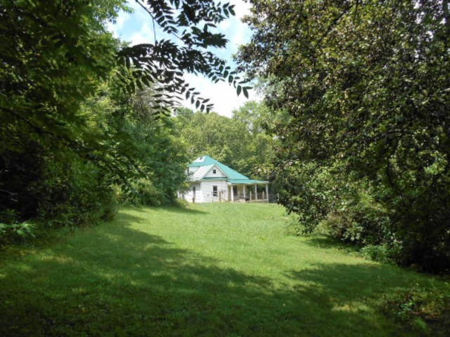 Roam your hideaway on an acre of lawns and woods, bordered by two creeks