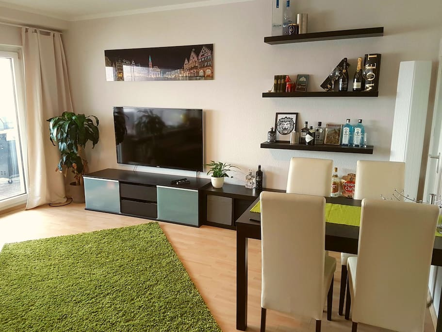 """Living room with new 60"""" cable TV. Table for dinner, work etc."""