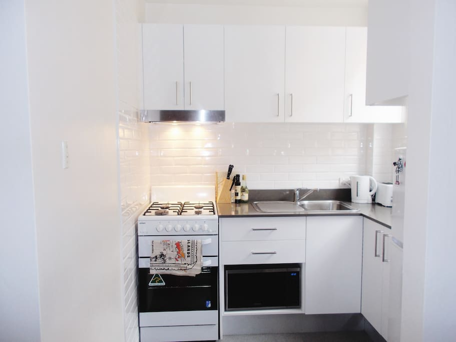 Fully equipped kitchen with oven, fridge, microwave, kettle.