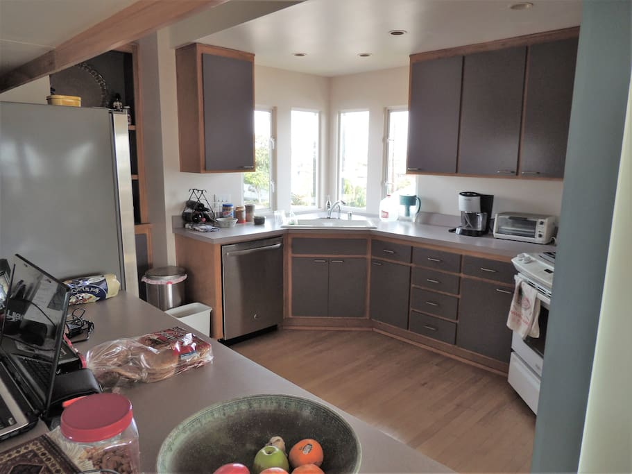 "Sunny, well appointed kitchen. Combined with adjacent dining room with views, you won't want to ""go out"" for meals."