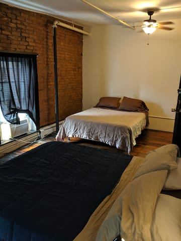 Picture 2 of Bedroom 1, which has 2 queen beds, a ceiling fan with light and a window AC unit, plus a night stand with lamp.