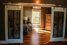 Barn doors offer privacy between bedroom and living room areas if someone is also sleeping on sofa~sleeper...French doors are to the right, leading to the private deck and hot tub