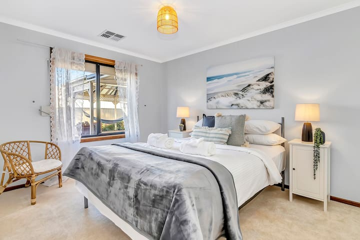 A second bedroom is very well lit and has a queen bed dressed in high-quality linen, bedside tables and charming decor