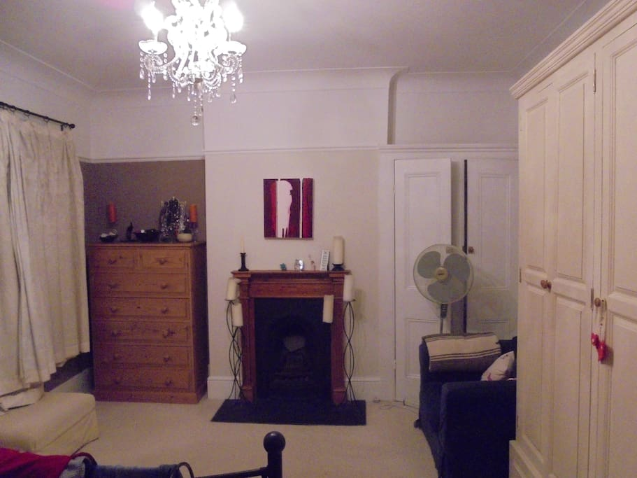 Other view of the bedroom showing chandelier, quaint open fireplace,  armchair and drawers