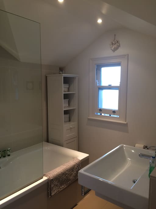 Private bathroom with large bath, overhead rain shower, large sink and toiletries provided if needed
