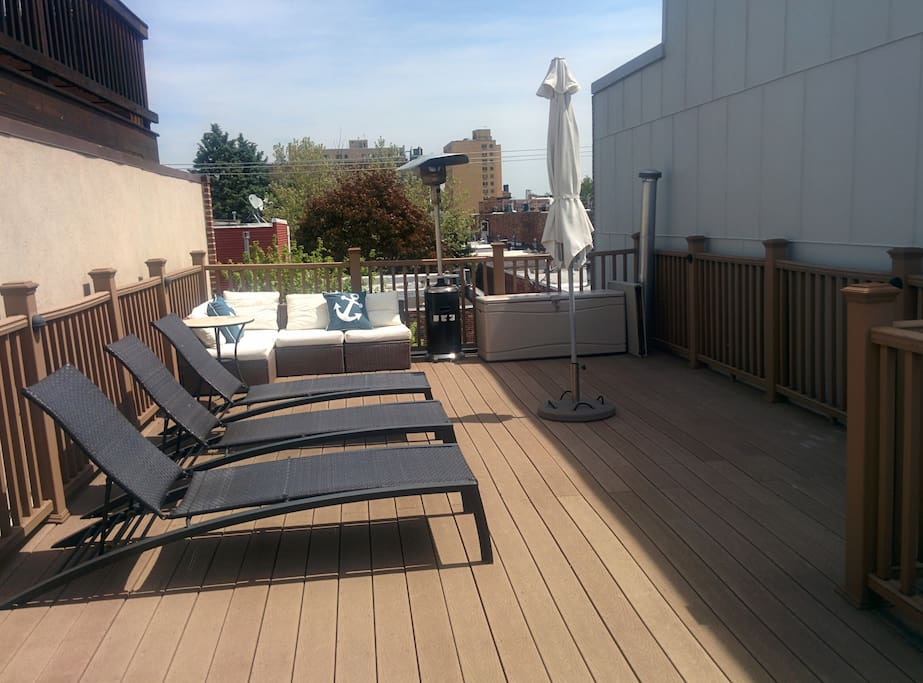 Roof deck with couch, chaise lounges, umbrella and grill.