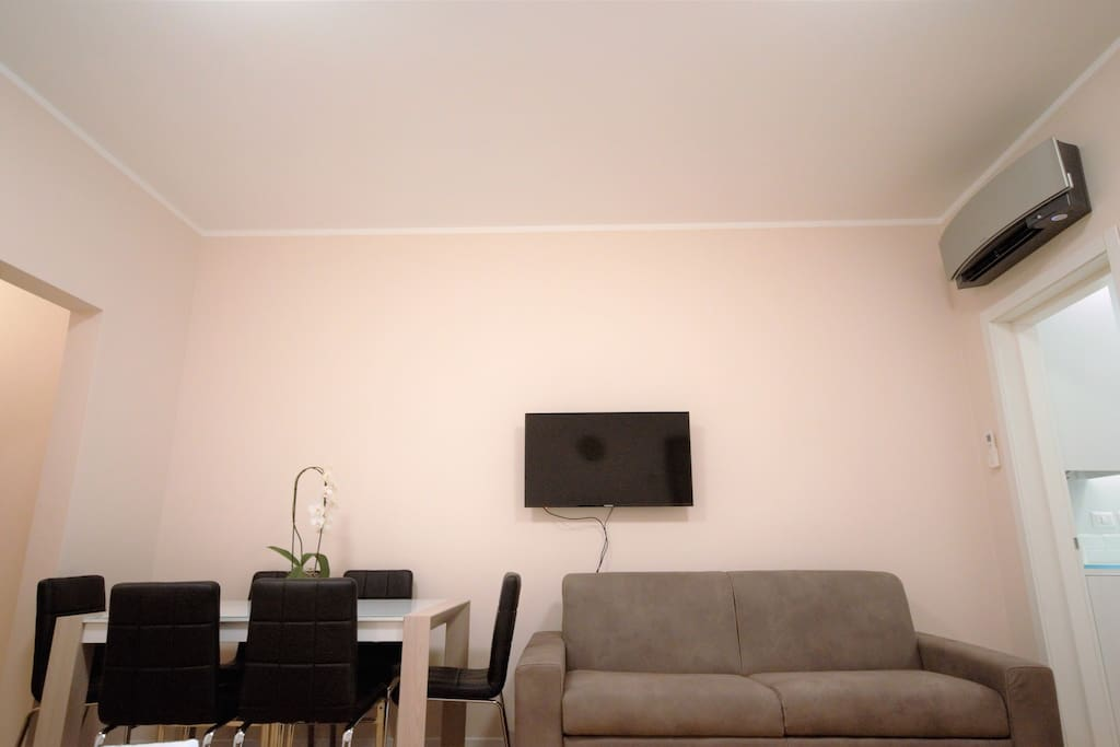 Living room with 2 sofabeds, table, chairs, Air Conditioner, window, TV, WIFI
