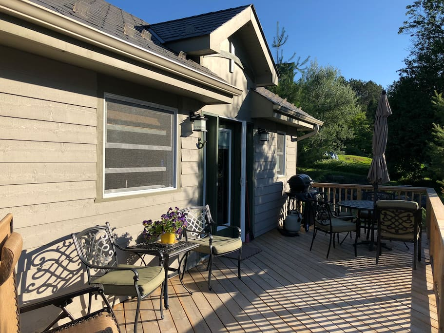 View of cottage with large,  private deck, outdoor furniture, propane BBQ
