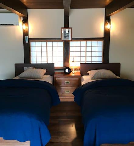 蔵サイトの8畳フローリングの部屋です、ベッドが2台が常備+折りたたみベッド1台があります。 掛布団は羽毛布団になります。 全室禁煙になっています。