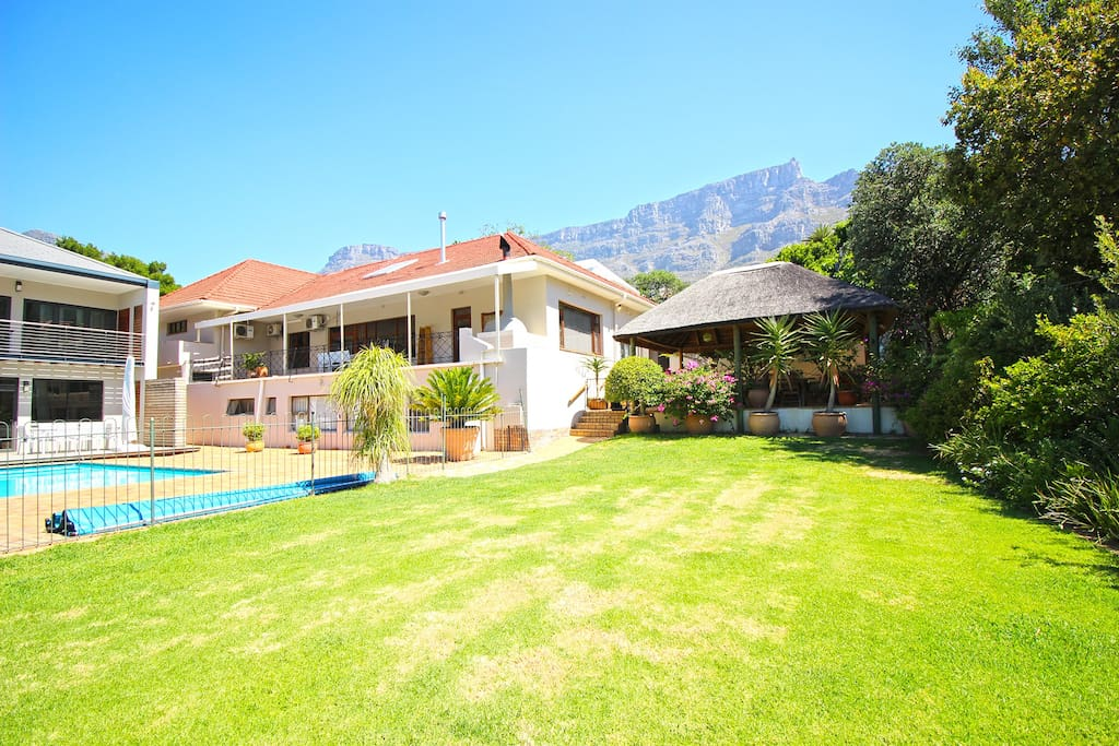 Owner's separate house (to the left), the main/guest house in the middle with thatched outdoor area, owner's garden and swimming pool which guests have access too. Table Mountain in the background