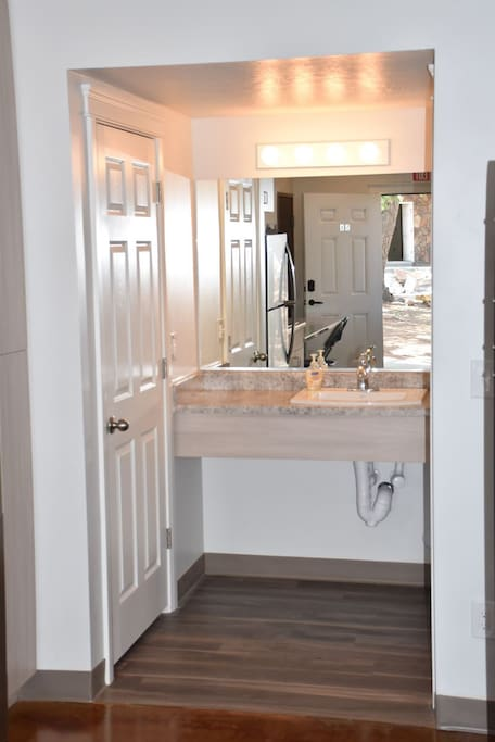 The vanity has plenty of room and is separate from the shower/toilet area