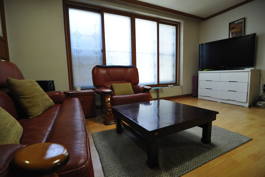 Shared living room with couches & big screen TV.