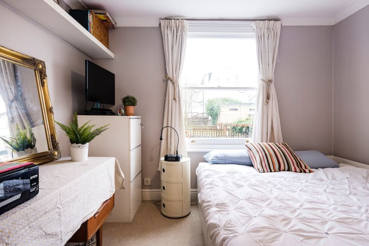 Bedroom with a view of the garden and canal, a kingsize bed, desk and fitted wardrobes. Adjoins a small bathroom with toilet and sink.