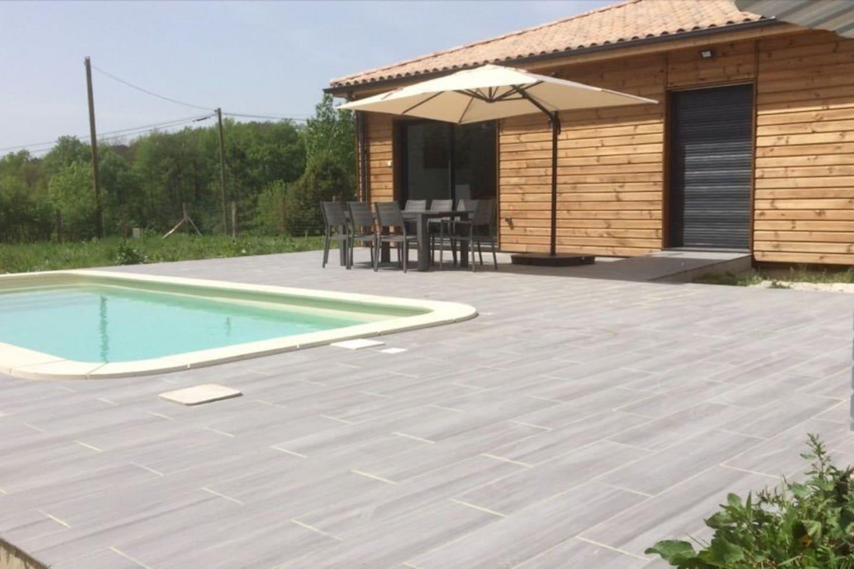 Terrasse avec piscine, table de jardin, parasol, bain de soleil et barbecue. Piscine protégée par une bâche á barre et une alarme.