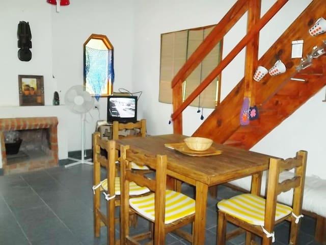 Una foto del living donde se ven las escaleras a las habitaciones y el baño