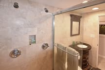 Bathroom features a tiled shower and double shower  heads