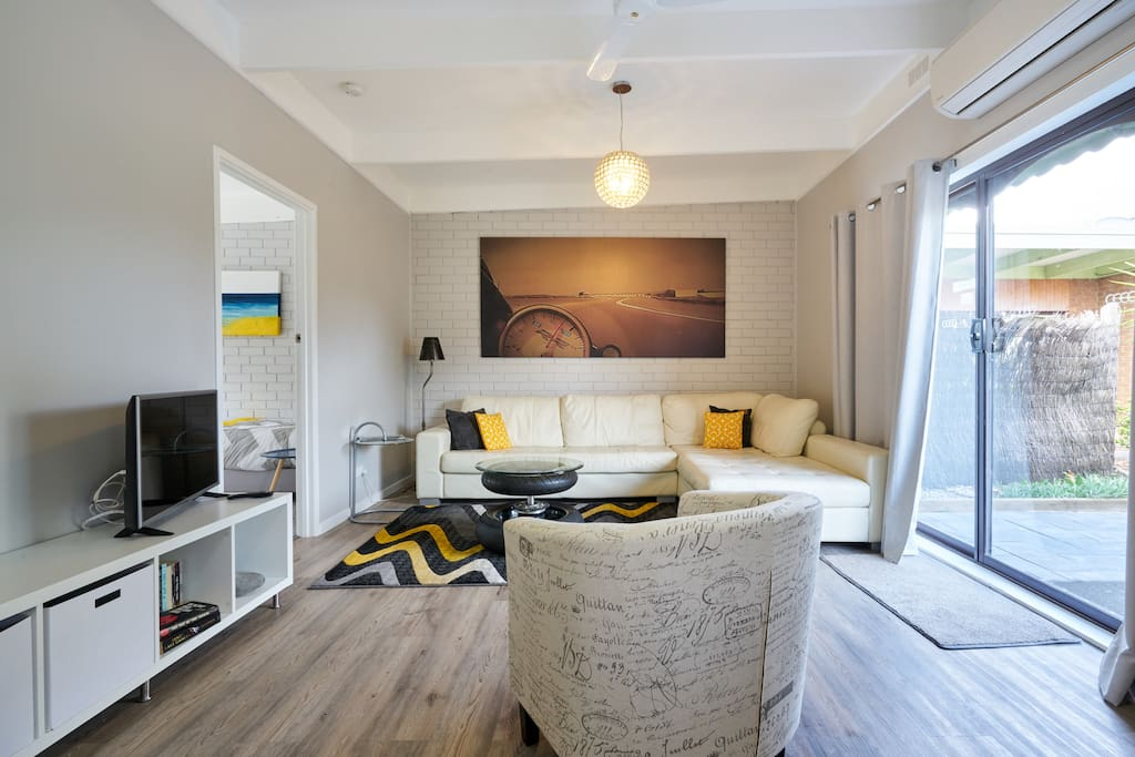 A large open plan lounge room with leather sofa, smart TV with free Netflix and Stan