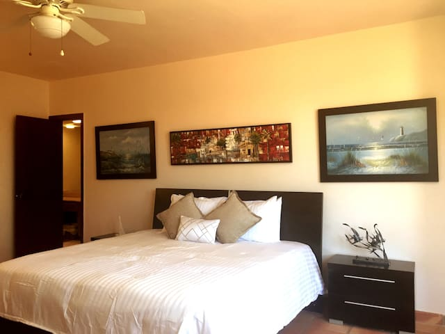 Master BR en-suite: King bed; Walk-In Closet; The drawer-vanity and the headboard are adorned with eye-catching, modern wall art. A large ceiling fan-light keeps the space breezy – while the triple, large bay-windows make this a bright, cheerful room