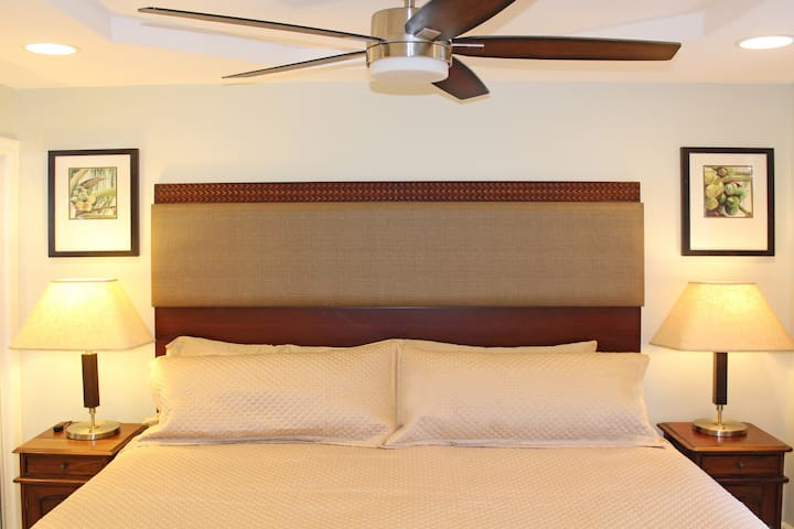 The bedroom has a comfortable King size bed and side tables with lamps; Ceiling fan above and portable air conditioner also.