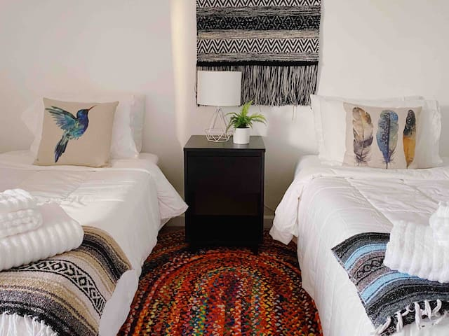 Guest bedroom features two twin-size beds, with comfortable premium linens/bedding