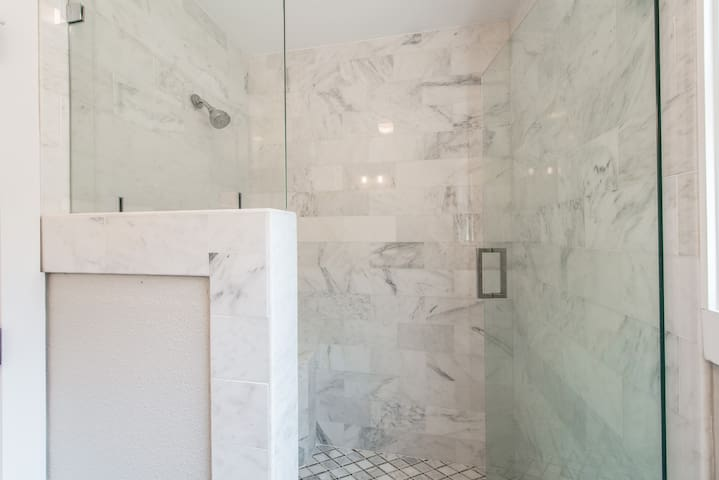 The master bathroom features a gorgeous marble walk-in shower.