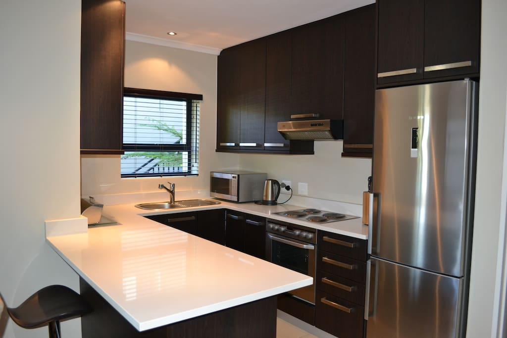 Fully fitted kitchen with stove, oven, fridge, microwave, utensils and cookware as well as washing machine.