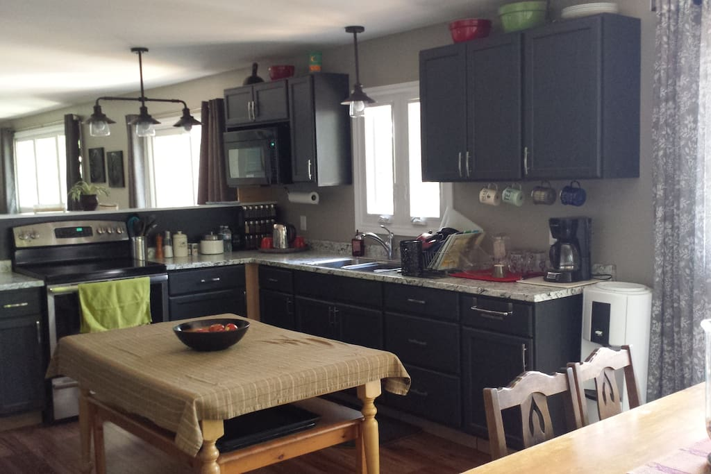 Kitchen view, table in place for groceries or additional seating.