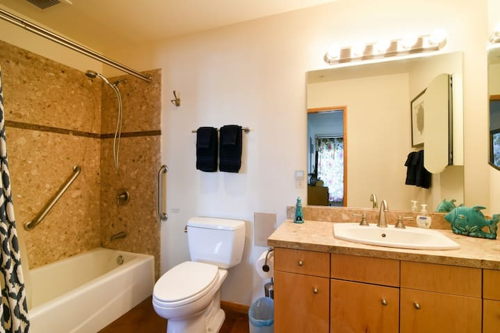 The bathroom connects to both bedrooms and has a shower and tub combo
