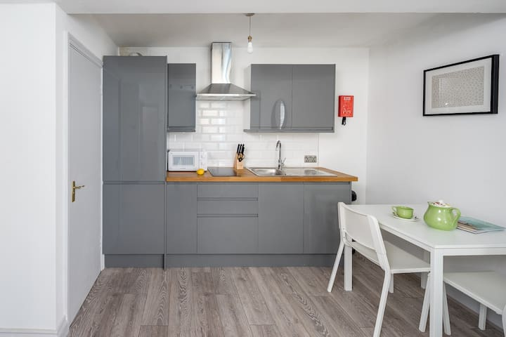 A small but well designed kitchen with microwave, small fridge, kitchen spaces and basics like kettle and toaster
