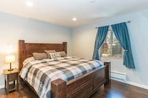 Master bedroom includes a luxurious king-size bed, tv, and USB chargers.