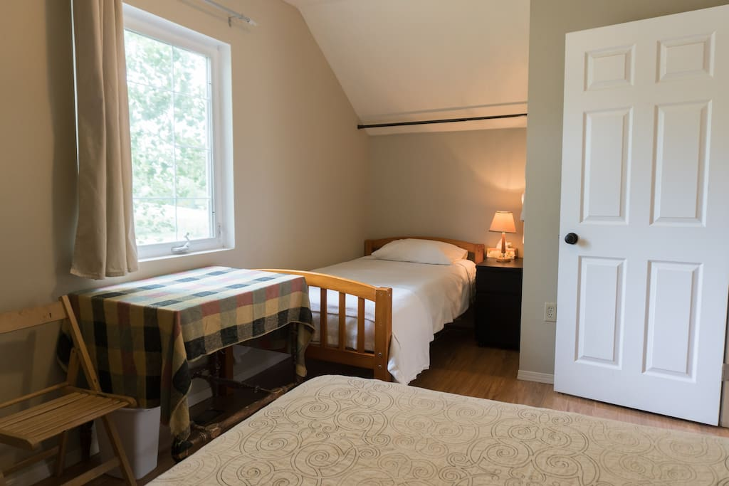 Private room with two beds, dresser and table. Twin bed can be used as a day couch