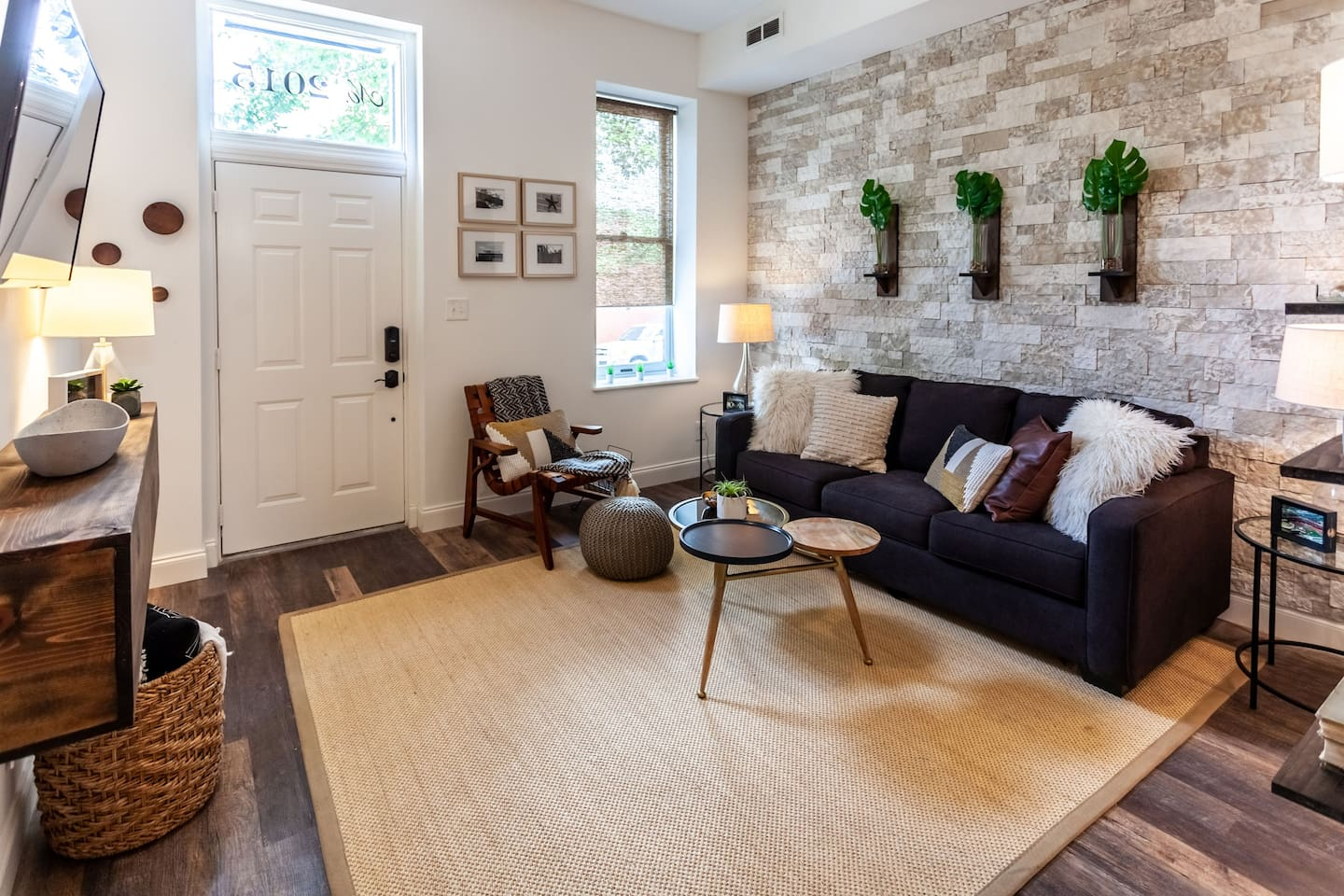 The front door is the center white door, this is the open concept living room as you walk in with stone wall, cable tv, and a relaxing living room.