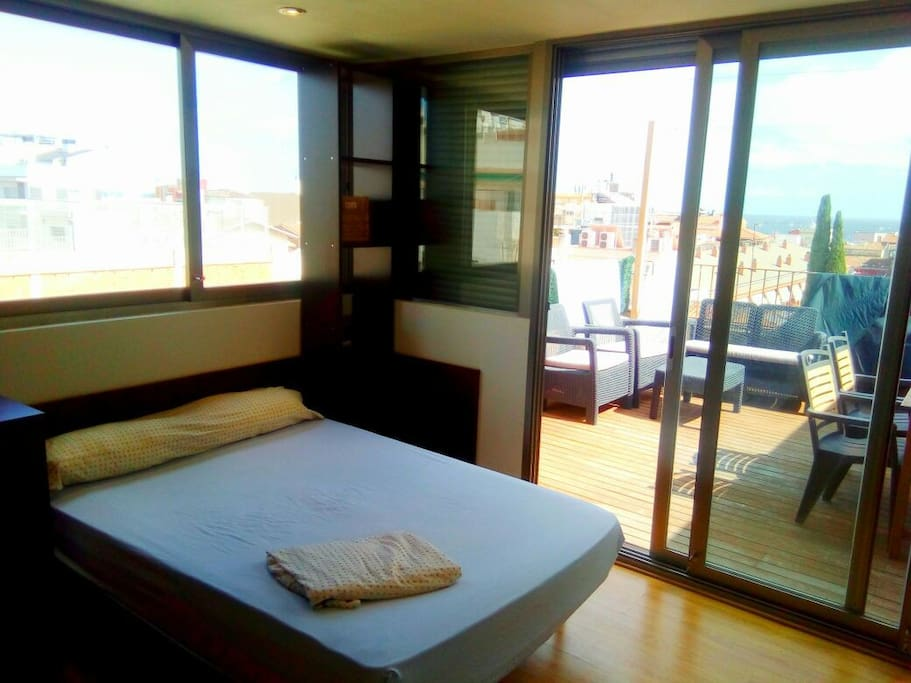 First room with double bed and  two bunch beds,  with private terrace,  bathroom and views to the see